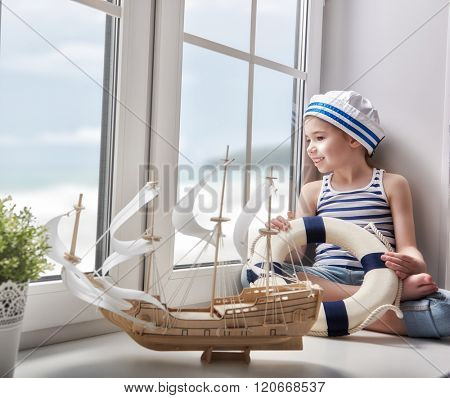 Adorable little child girl sitting on the window and holding lifeline. Girl looks at the blue sky and dreams of sea, adventures and travel. Girl has a toy ship.