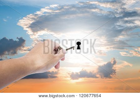 Hand holding golden key extending to unlock on sunset sky, business abstract concept
