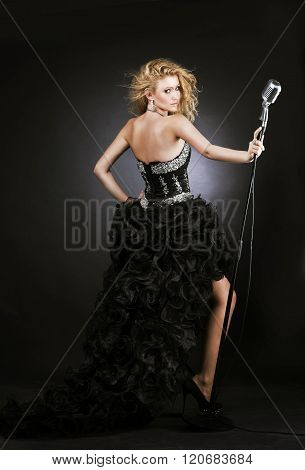 Beautiful Girl Singer In Black Dress With Microphone On The Stage.