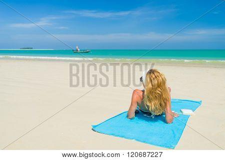 Woman in bikini suntanning at the tropical beach