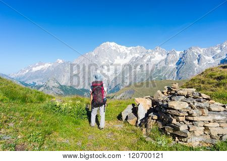 Backpacker Hiking On The Alps, Majestic Mont Blanc In Background