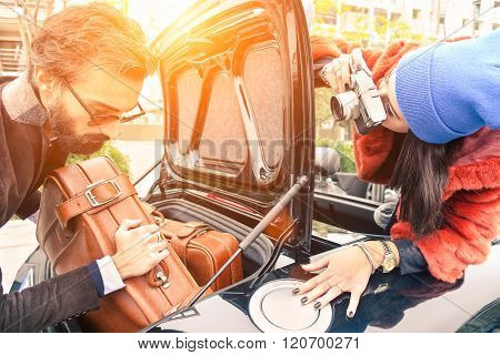 Hipster Fashion Couple Having Fun At Loading Leather Travel Suitcase In Sportscar