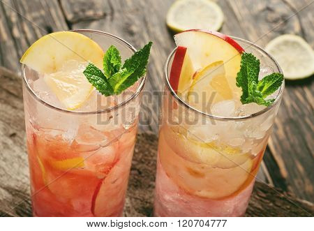 Two Cranberry Cocktail With Ice, Mint, Lemon And Apple