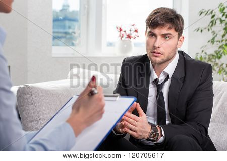 Depressed businesman talking with psychologist