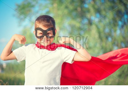 Super Hero Kid having fun outdoor. Superhero little boy over nature green blurred background showing muscles. Little boy wearing superhero costume and having fun outdoors