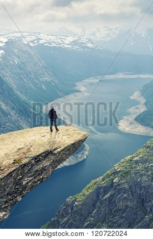 Woman On Trolltunga -  View On Norway Mountain Landscape From Trolltunga - The Troll's tongue in Odda, Ringedalsvatnet Lake,  Norway).