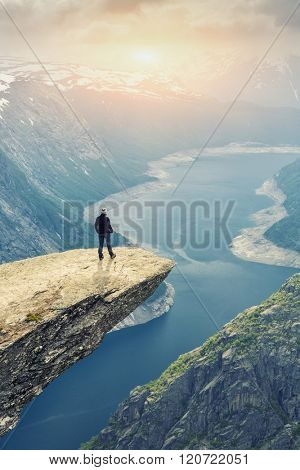 Woman On Trolltunga -  View On Norway Mountain Landscape At Sunset From Trolltunga - The Troll's tongue in Odda, Ringedalsvatnet Lake,  Norway).