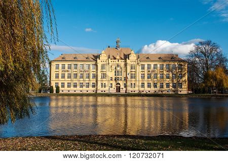School building in the mirror of pond in Litovel, Czech Republic