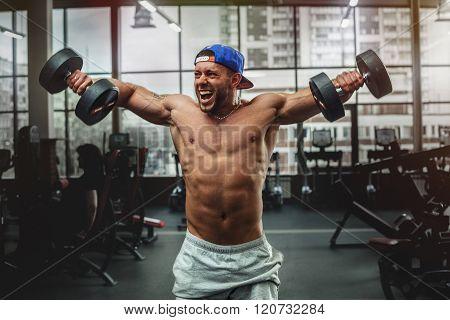Handsome man lifting dumbbells at gym.