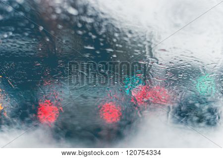 Road view through car window with rain drops and melting snow