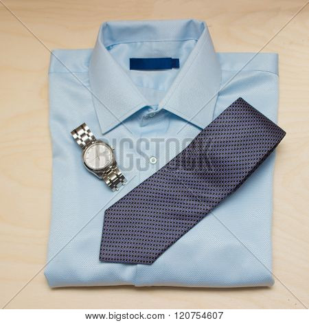 Blue shirt, silver watch and tie on wooden background