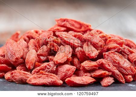 Pile Of Goji Berries On A Black Stone Plate