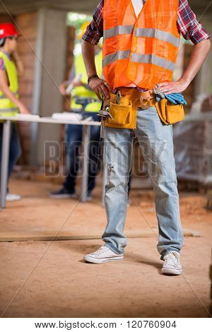 Close up view of workers belt with tools and protective vest