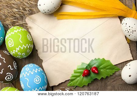 Easter card. Painted Easter eggs with piece of paper for congratulation on a natural wooden backgrou