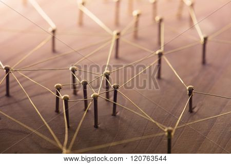 Linking entities. Network, networking, social media, connectivity, internet communication abstract. Web of thin gold wires on rustic wood.