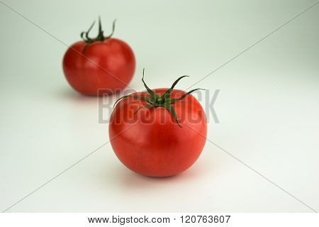 Two red ripe tomato with long sepal leaves still intact. Isolated on natural white background.