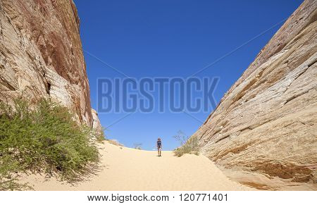 Young Woman Walking On Sand Between Great Rock Formations, Usa.