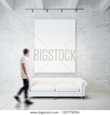 Photo of man in gallery. Waching empty canvas hanging on the brick wall and vintage classic sofa woo