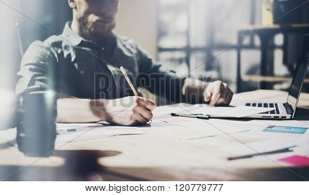 Photo bearded architect working with new project. Generic design notebook on wood table.  Analyze pl