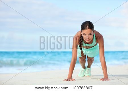 Fitness beach woman smiling planking doing yoga exercises. Happy Asian girl training her abs exercising her core muscles with the plank pose.