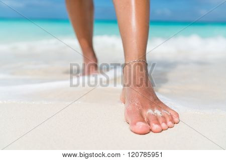 Beach feet closeup - barefoot woman walking in ocean water waves. Female young adult legs and toes wearing an ankle bracelet anklet relaxing in summer vacation travel. poster