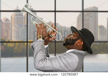 Black trumpeter performing at daytime.