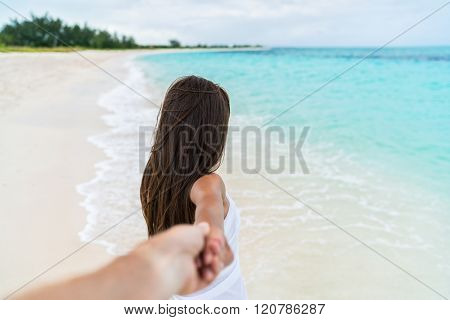 Couple summer vacation travel - Woman walking on romantic honeymoon beach holidays holding hand of boyfriend following her, view from behind. POV.
