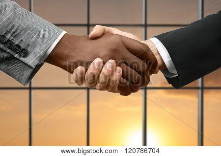 Men shake hands beside window.