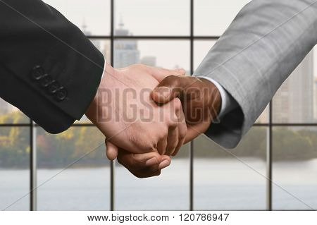 Businesspeople shake hands at daytime.