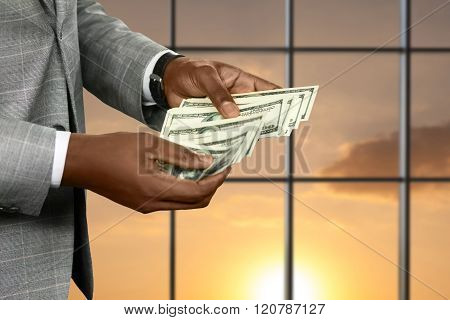 Black office employee counts income. Manager counting money at sunset. The fortune in his hands. Enjoy while you can. poster
