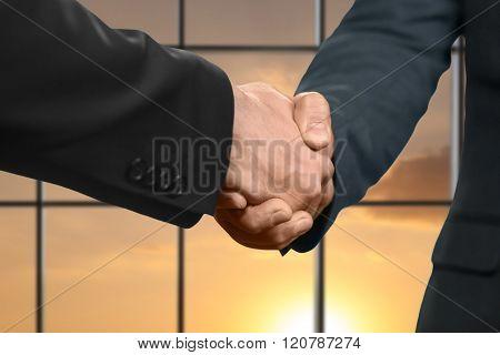 Men's sunset handshake in office.