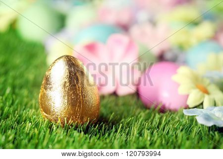 Colorful Easter eggs on grass with golden egg