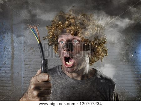 young man with funny curly wig holding electrical cable smoking after domestic accident with dirty burnt face and shock electrocuted expression in electricity DIY repairs danger concept in black smoke background