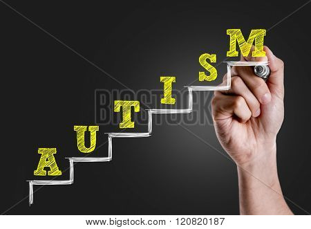 Hand writing the text: Autism