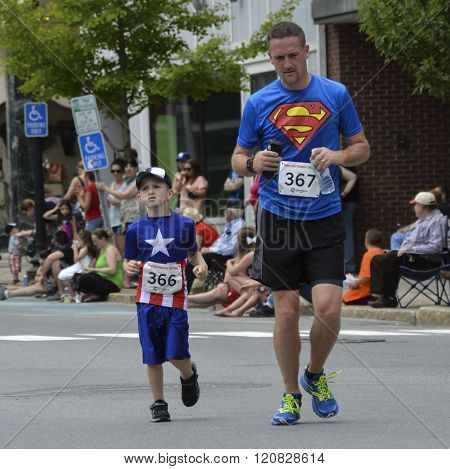 Bangor, Maine/USA-July 4: A dad with a Superman t-Shirt, and his son with a Captain American t-shirt run the 4th of July Parade race preceding the event in Bangor, Maine in 2015.