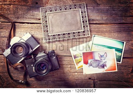 Old photographic camers with vintage prints and photo frame on wooden desk
