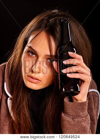 Drunk girl keeps bottle of alcohol. Soccial issue addict alcoholism. Black background.