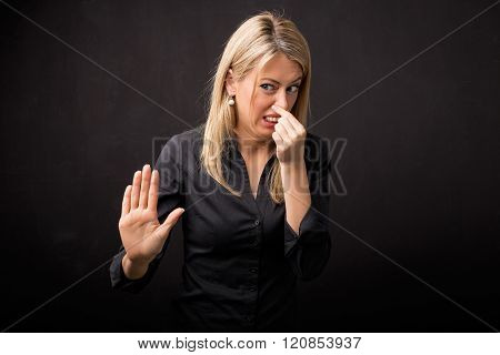 Woman holding her nose in disgust and holding her hand out