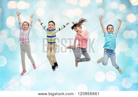happiness, childhood, freedom, movement and people concept - happy little children jumping in air over blue holidays lights background