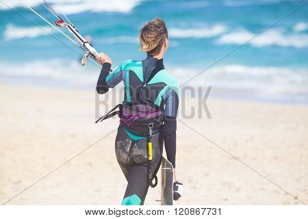 Female kiteboarder with kiteboarding equipment.