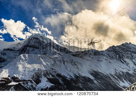 Mountain rescue helicopter in Himalaya Mountains on background of the Annapurna Himal ridge. Dramatic rescue action in white winter high mountains Nepal.