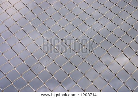 Metal Security Fence With A Dark Cloudy Background.