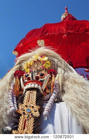 Rangda Mask under red umbrella in temple - traditional spirit of Bali at ceremony Melasti before Balinese New Year and silence day Nyepi Holidays festivals rituals art culture of Indonesian people poster