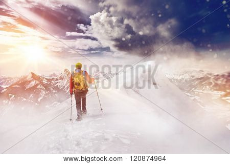 Person cross country skiing or Nordic walking or hiking in a beautiful snow covered mountain landscape facing towards the glow of the rising sun and rugged alpine peaks