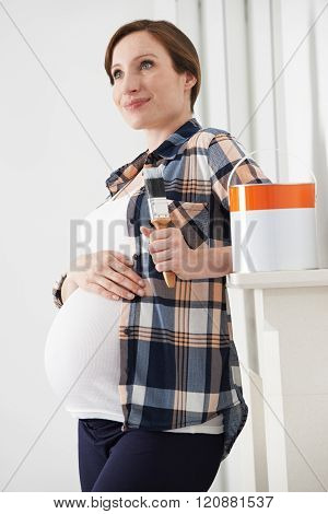 Pregnant Woman Taking Break Whilst Decorating Nursery