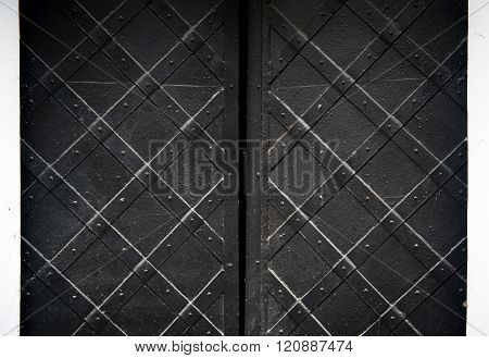 texture of black old metal door with rivets for background