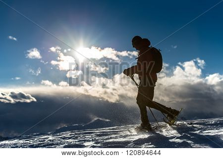 Man Walking In The Snow With Snowshoes