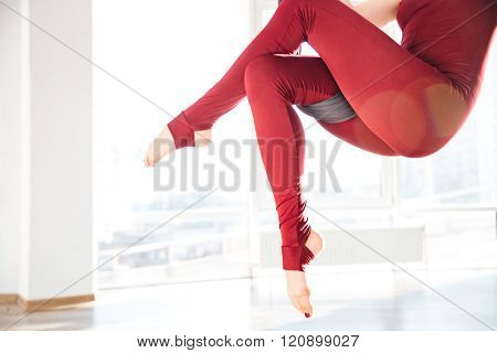 Closeup of slim woman legs in leggins doing aerial yoga exercise in studio
