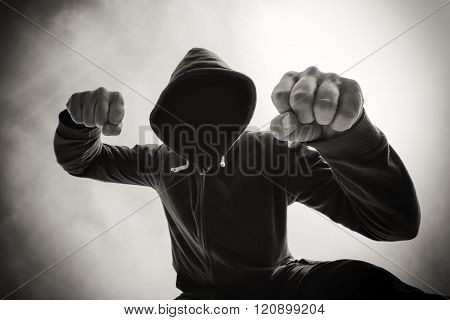 Street agression being punched and mugged by aggressive violent man in hooded jacket on street victim's pov perspective monochromatic black and white image. poster