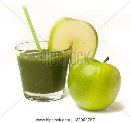 A glass of apple smoothie with a drinking straw, with a wedge of an apple and a whole apple